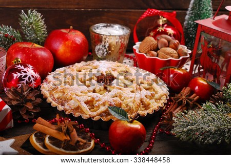 traditional apple pie with ingredients and decoration for christmas on wooden rustic table - stock photo