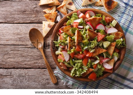Traditional Arabic fattoush salad on a plate on the table. horizontal top view