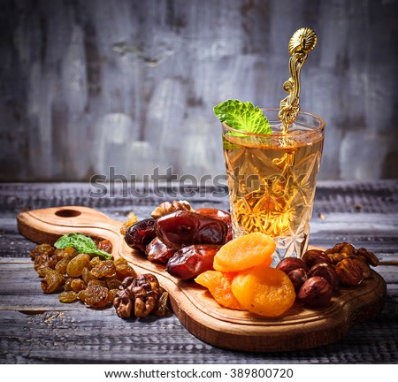 Traditional arabic tea and dry fruits. Selective focus, toned - stock photo