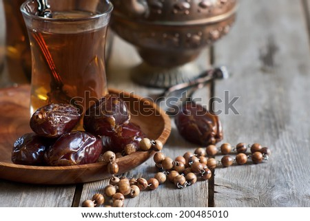 Traditional arabic tea with wooden rosary and dry madjool dates . Selective focus. - stock photo