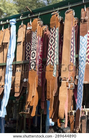 Traditional Argentinean leather gaucho belts hanging on for sale on a fair in Rosario city, Argentina - stock photo