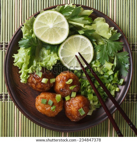 Traditional Asian fish balls with lime and fresh herbs and chopsticks on a bamboo table close-up. top view  - stock photo