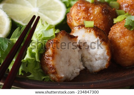Traditional Asian fish balls with lime and salad on a plate macro. horizontal  - stock photo