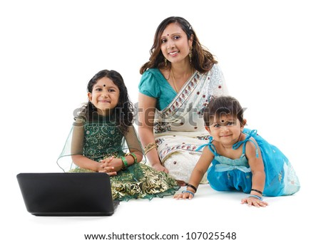 Traditional Asian Indian family using laptop computer over white background