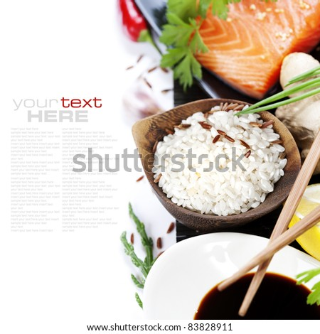 traditional asian ingredients (Fresh salmon steak filet, uncooked rice, ginger, lemon,  soy sause and chopsticks) over white with sample text - stock photo