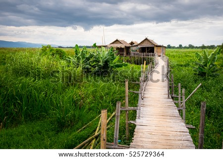 Traditional Asian local farm houses and wooden bridge, Inle lake, Myanmar (Burma)