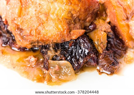 Traditional baked pork with dried plums and walnuts. Macro. Photo can be used as a whole background.