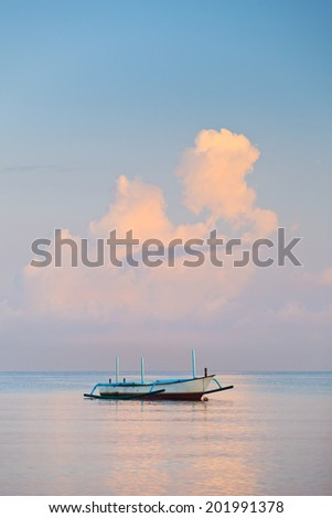 traditional Balinese ships Jukung close on Sanur beach at sunrise or sunset, Bali Indonesia - stock photo