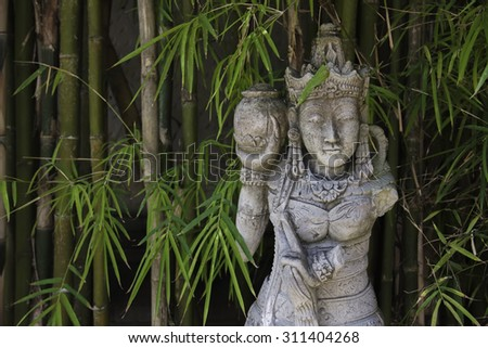 Traditional Balinese stone sculpture in bamboo forest at Bali,  Indonesia - stock photo