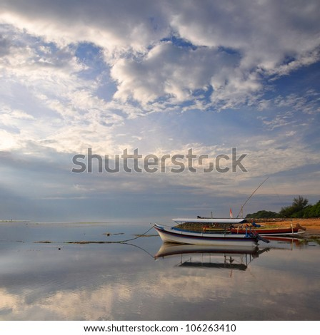 Traditional Balinese wooden glass bottom tourist boats moored off Sanur Beach at dawn, Indonesia. Large Vertical Panorama composition with lots of copy space. - stock photo