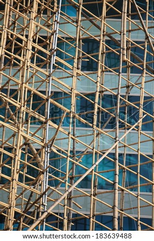 traditional bamboo Scaffolding big project in front of modern office glass building in hong kong, Asian housing tech - stock photo