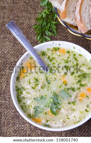traditional barley soup in a white bowl with bread