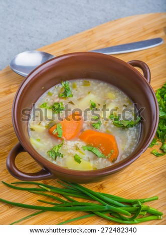 Traditional barley soup with parsley in a dark bowl  - stock photo