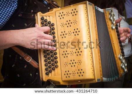 Traditional Bavarian accordion player playing folk music in Austria - stock photo