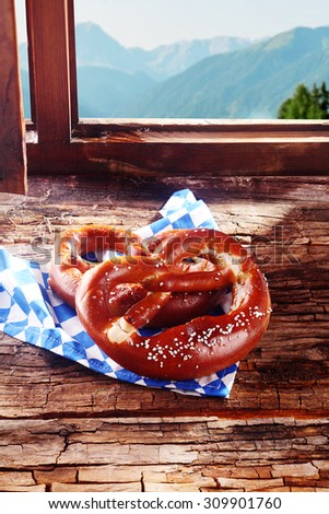 Traditional Bavarian pretzel, a brittle dried glazed and salted knotted biscuit, served in a tavern for a lunchtime snack o a window sill overlooking the alps outside - stock photo