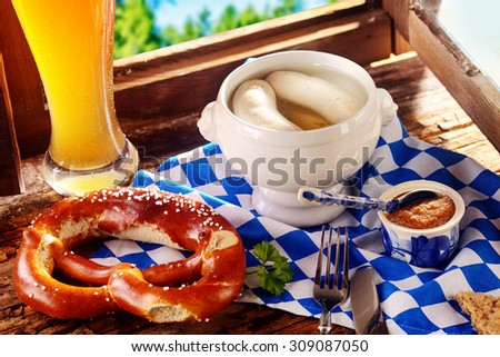 Traditional Bavarian tavern cuisine for a tasty midday snack with white veal sausages in broth served with a crispy knotted pretzel, sauce and a long glass of cold beer - stock photo