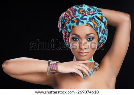 Traditional beauty. Beautiful African woman in headscarf and jewelry posing against black background and looking at camera - stock photo