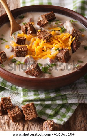 Traditional beer soup with bacon, cheddar cheese and croutons in a bowl close-up on the table. Vertical - stock photo
