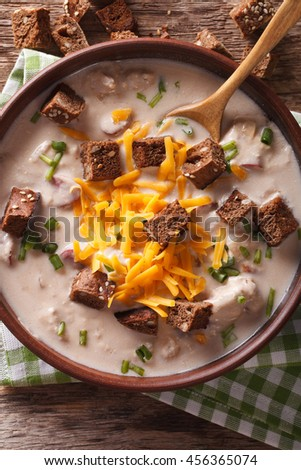 Traditional beer soup with bacon, cheddar cheese and croutons in a bowl macro on the table. Vertical view from above - stock photo