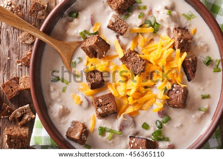 Traditional beer soup with bacon, cheddar cheese and croutons in a bowl macro on the table. horizontal view from above - stock photo