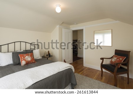 Traditional beige bedroom with wooden chair and peaked roof.  - stock photo