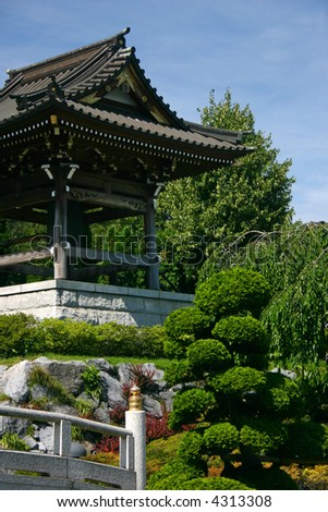 traditional bell tower of a japanese temple in a botanical garden with bridge - stock photo