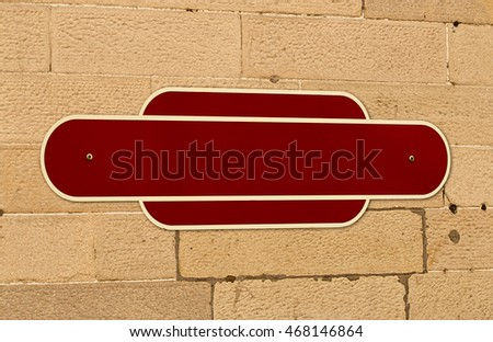 Traditional blank railway sign on the wall of a train station for insertion of your message or place name in middle.