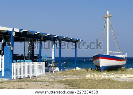 Traditional blue and white Greek  tavern restaurant with sea view and a boat, Greece,Kos. - stock photo