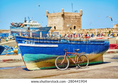 Traditional blue fishing boat and old bicycle in the port of Essaouira, Morocco - stock photo