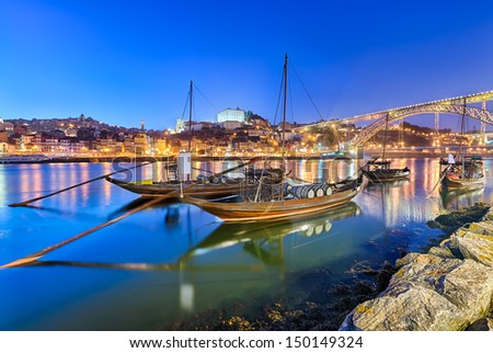 Traditional boats on the Douro river in Porto, Portugal with the Dom Luiz bridge in the background - stock photo
