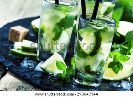 Traditional Brazilian caipirinha alcoholic cocktail with lime, mint and brown sugar, selective focus - stock photo