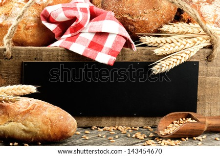 Traditional bread and rustic wooden board with copyspace - stock photo