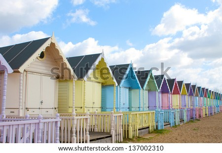 Traditional British beach huts on a bright sunny day - stock photo