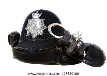 traditional british police helmet and handcuffs isolated on white - stock photo