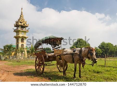 traditional burmese horse cart with wooden wheels used for transport and to cart around tourists in front of Paleik snake temple, Burma - stock photo