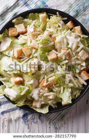 Traditional Caesar salad with croutons and parmesan close-up on a plate. vertical top view  - stock photo