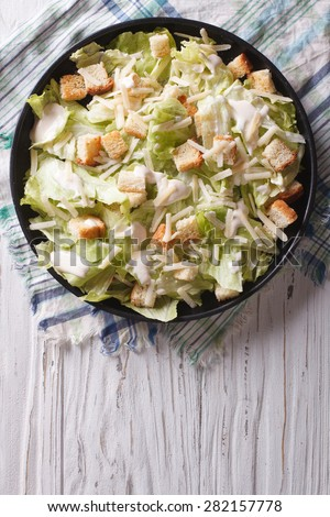 Traditional Caesar salad with croutons and parmesan on a plate. vertical top view  - stock photo