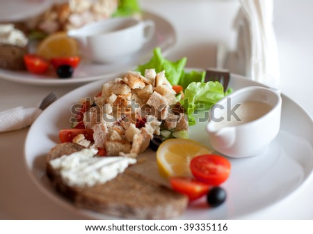 traditional caesar salad with sauce-boat and bread