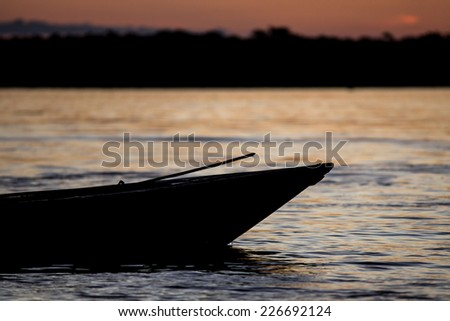 Traditional canoe silhouette on the Amazon river in Iquitos, Loreto, Peru - stock photo