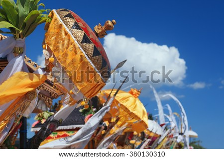 Traditional ceremonial umbrellas and flags on beach at ceremony Melasti before Balinese New Year and silence day Nyepi. Holidays, festivals, rituals, art, culture of Indonesian people and Bali island. - stock photo