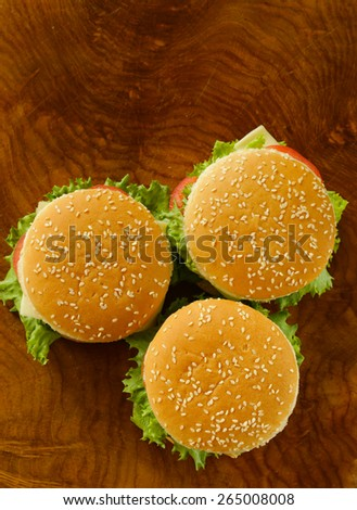traditional cheeseburger with green lettuce and tomatoes on wooden background top view - stock photo