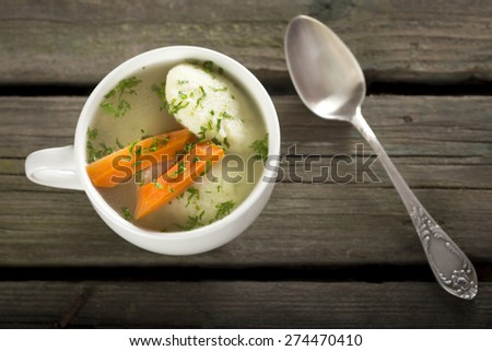 Traditional Chicken Soup with dumplings on a rustic wooden table with silver spoon - stock photo