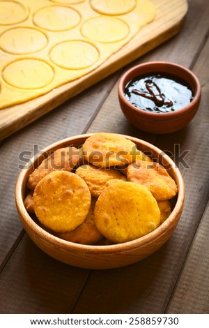 Traditional Chilean Sopaipilla fried pastry made with mashed pumpkin in the dough, served with Chancaca sweet sauce, photographed with natural light (Selective Focus, Focus on the first sopaipillas) - stock photo