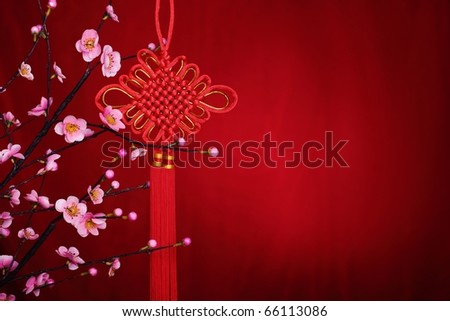 Traditional chinese decorative knot and plum blossom on a festive background. - stock photo