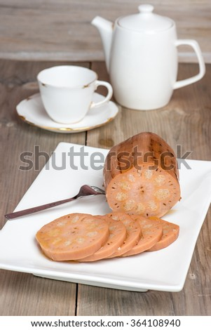 Traditional Chinese dessert / side dish - Lotus root stuffed with glutinous rice, drizzled with maple syrup. Antique /vintage fine bone china table ware, on weather wood table. - stock photo