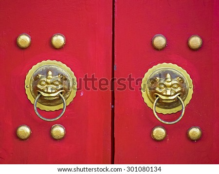 Traditional Chinese doors with brass handles symbolic of lion's heads. It's believe to ward off evil and usher in good luck for the occupants. - stock photo