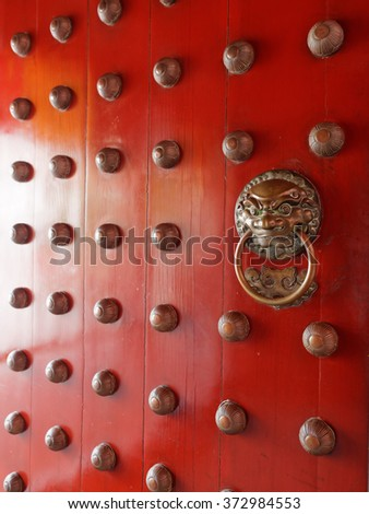 Traditional Chinese doors with brass handles symbolic of lion's heads. It's believe to ward off evil and usher in good luck for the occupants.