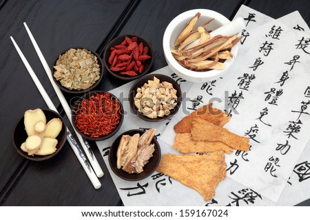 Traditional chinese herbal medicine selection with mandarin calligraphy on rice paper. Translation describes the medicinal functions to maintain body and spirit health and balance energy. - stock photo