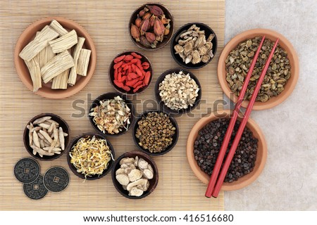 Traditional chinese herbal medicine with herb selection, i ching coins and chopsticks over bamboo background. - stock photo