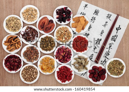 Traditional chinese herbal medicine with mandarin calligraphy  on rice paper. Translation describes the medicinal functions to maintain body and spirit health and balance energy.  - stock photo